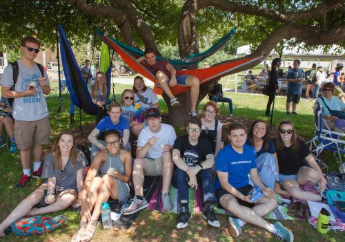 Group of students sitting together under a tree during Orientation