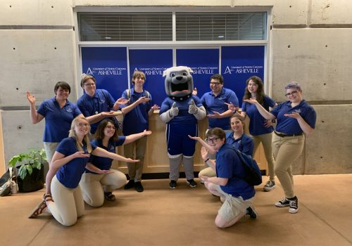 The UNC Asheville Blue Crew posing with the mascot Rocky