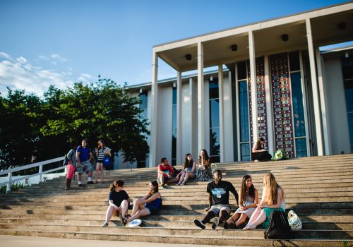 Students sitting on steps in front of Ramsey Library