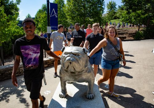 Students patting Rocky the Bulldog statue for good luck